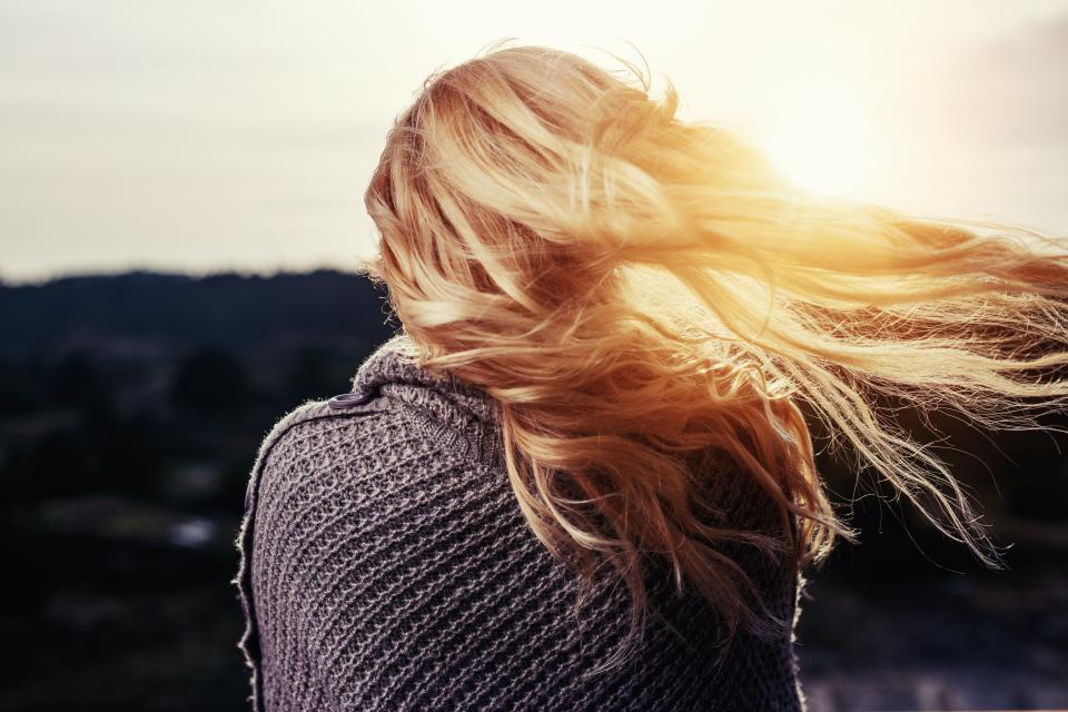 cabelos iluminados da mulher que olha o horizonte
