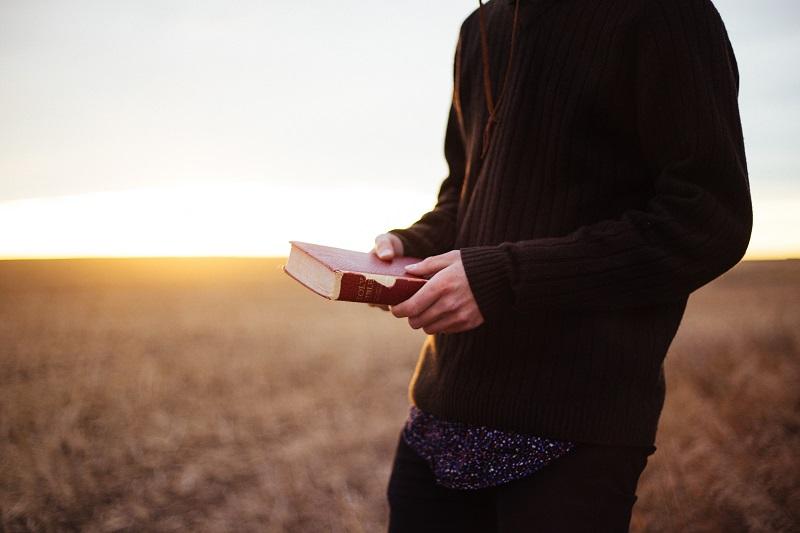 Homem no campo segurando o livro com uma mensagem